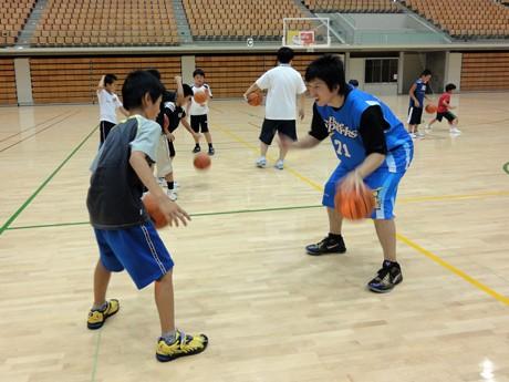 参加児童にドリブルを教える近内選手(右)
