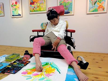 足の指で絵筆を挟み、花の絵を描く山口さん