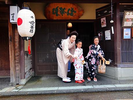 打ち水をする「こども女将」の岡島百那ちゃん(中央)と馬場華さん(右)