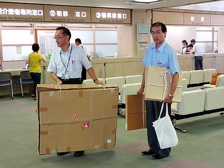 会場となる待合ホールで作品を運ぶ職員