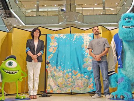 「モンスターズ・ユニバーシティ」のキャラクターをちりばめた加賀友禅振り袖と、製作者の上坂さん(左)、マンさん