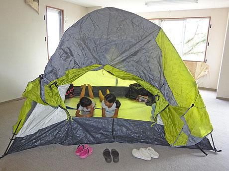 ビルの室内にテントを張り、寝転がる子どもたち