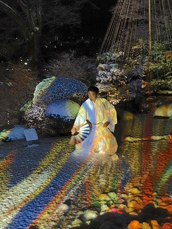 夜景を絶妙の借景とする高台の庭へモリ川さんの作品がプロジェクションされた中、即興の踊りを披露する藤間さん