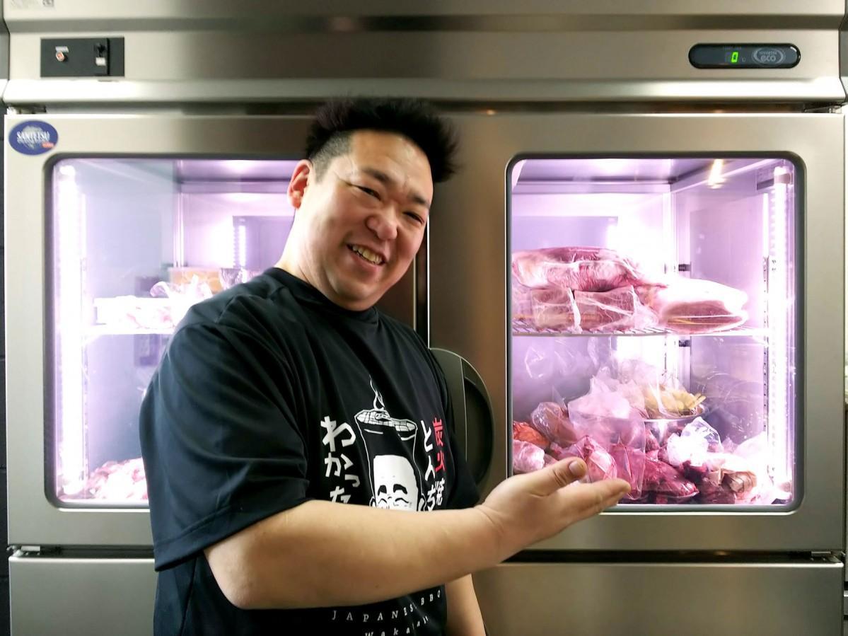 和牛の鮮度を保つ専用の冷蔵庫と店主の佐藤浩之さん