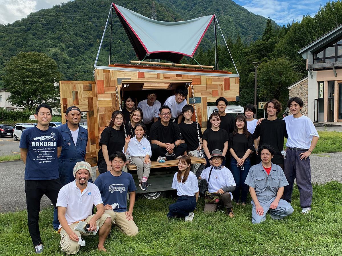 完成を祝う金沢工大の宮下智裕准教授と学生、地域の人たち