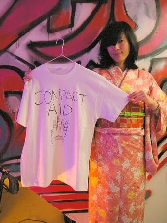「COMPACT AID!」のためにデザインしたTシャツを掲げる工藤キキさん