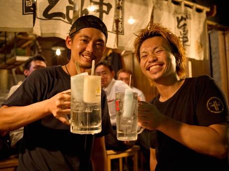 栗原大弥店長(左)と「どまん中サワー」を手にするスタッフの中村篤典さん(右)
