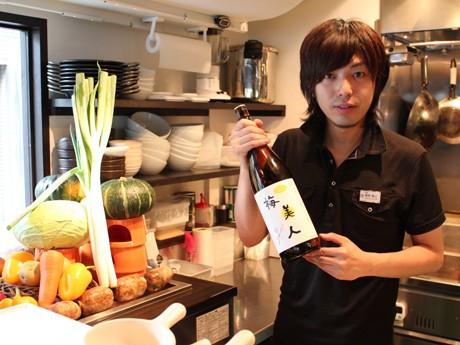 当日仕入れた野菜に囲まれた店長代理の粟野さん。手に持つのは「女性におすすめ」のコラーゲン入り梅酒「梅美人」