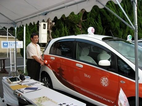 出発式に参加してEV(電気自動車)タクシーに充電をする清野吉光さん。