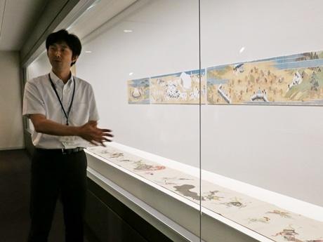 学芸員の村野さんと付喪神の行列を描いた「百鬼夜行絵巻」