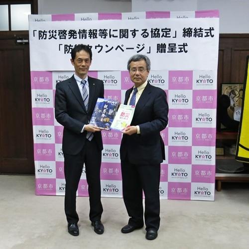 タウンページと防災タウンページを手にする植村副市長(左)と岡田NTTタウンページ社長(右)