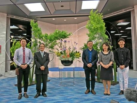 両端がイケノボーイズの藤井さんと柿沢さん(左から2番目から)宮田長官と篠原監督、池坊専好次期家元。後ろが完成した作品。