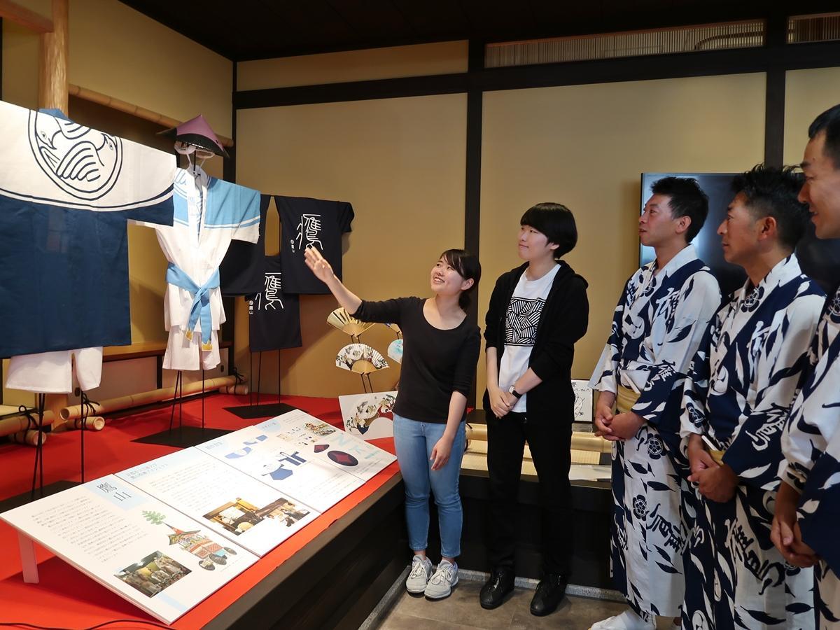 出来上がった衣装を鷹山の囃子方に見せる佐藤さんと石田さん