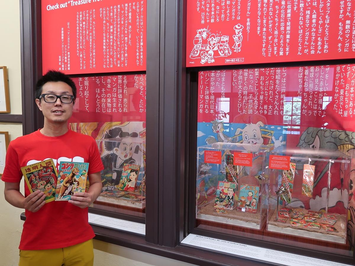 赤が目に飛び込む展示と研究員の伊藤遊さん
