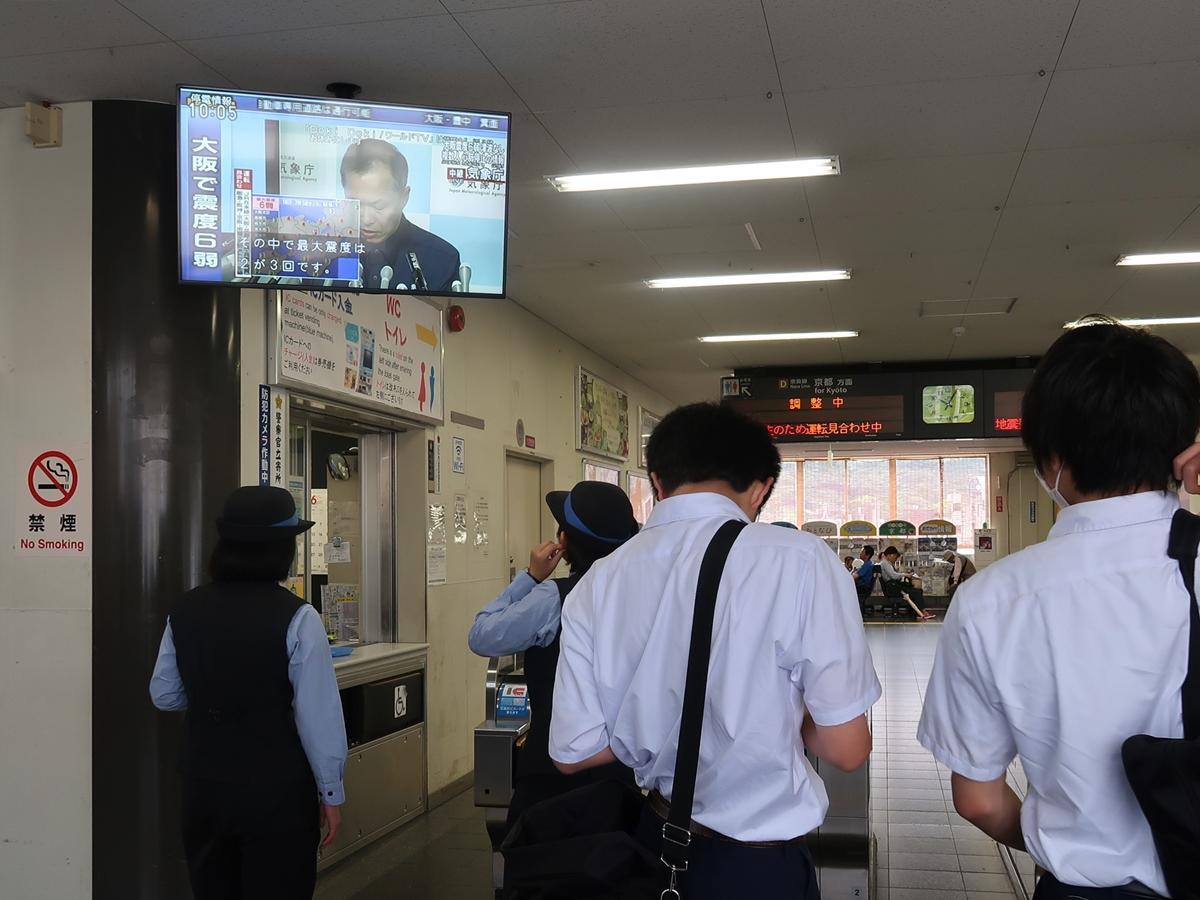 気象庁の発表を見つめるJRの駅職員