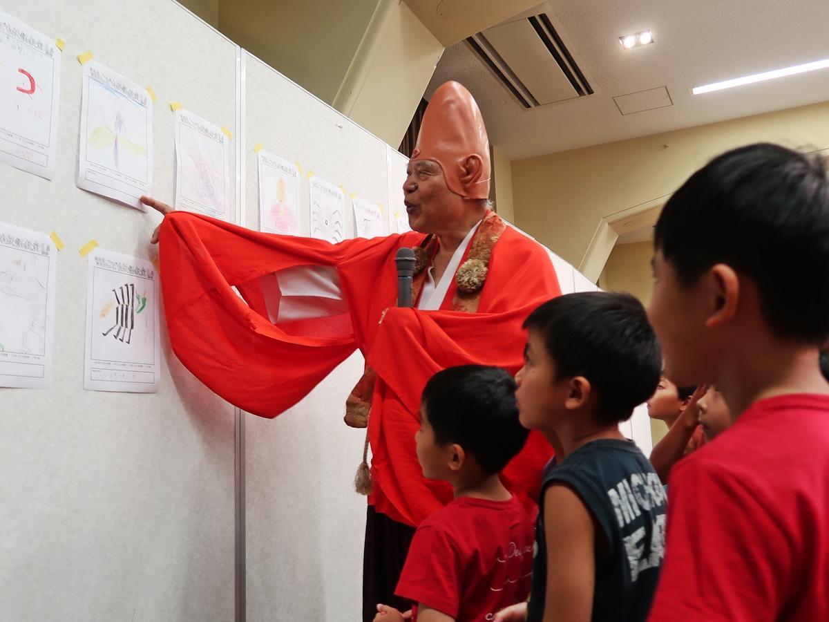 子どもたちの描いた妖怪を評価する荒俣館長