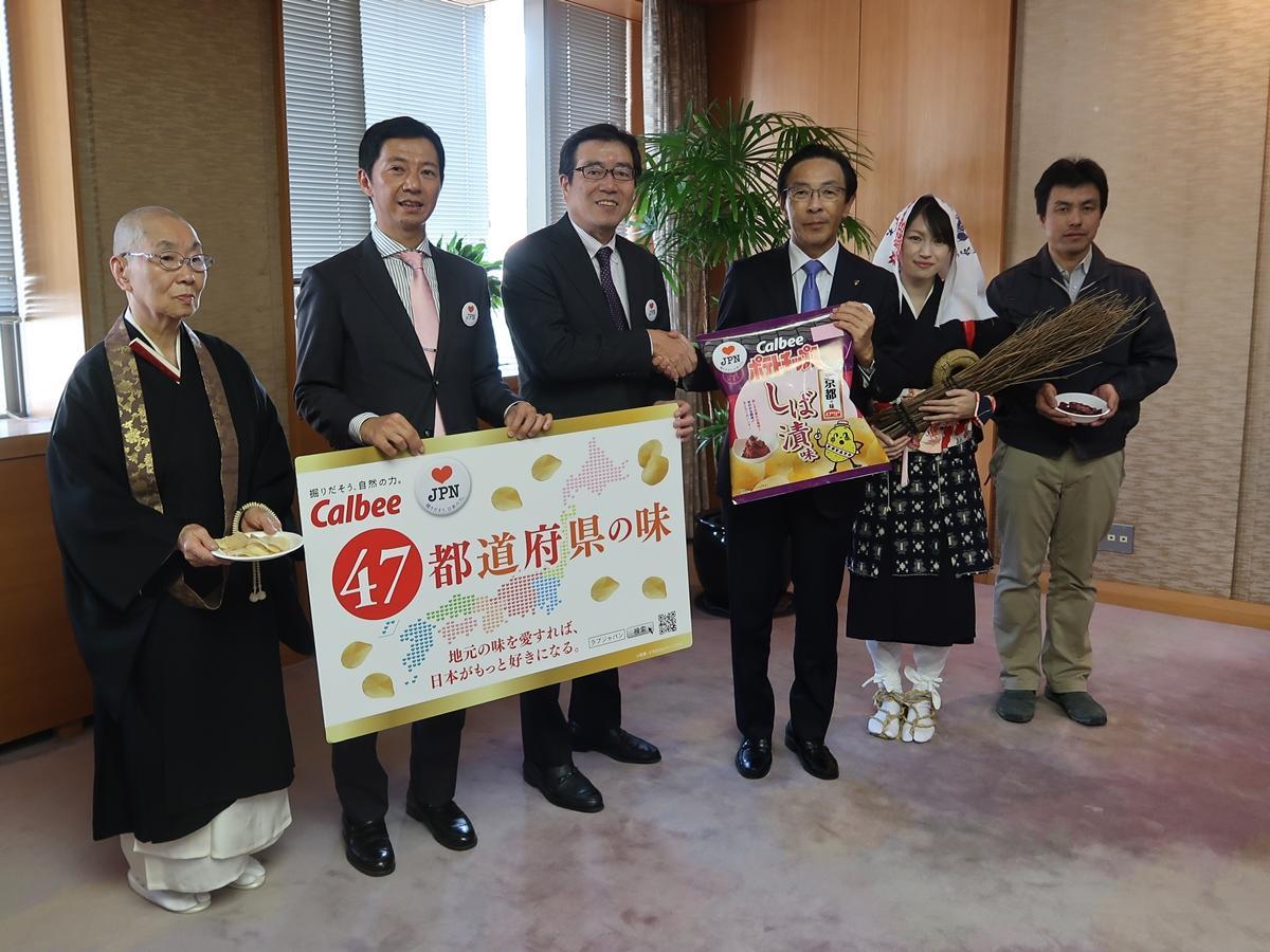 握手を交わす伊藤社長と西脇府知事。伊藤社長はしば漬け色のネクタイとシャツのコーディネートで登場した