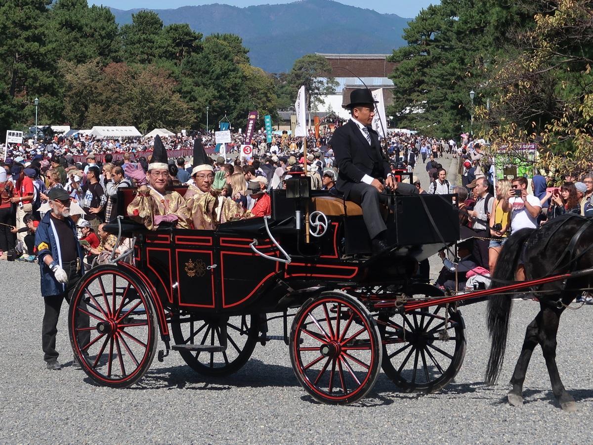 沿道の観客に手を振る西脇京都府知事(右)と門川大作京都市長(左)