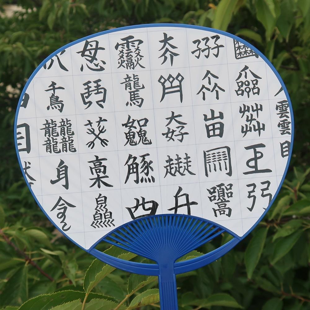 難しい漢字が並ぶうちわ。文字はスタッフの手書き