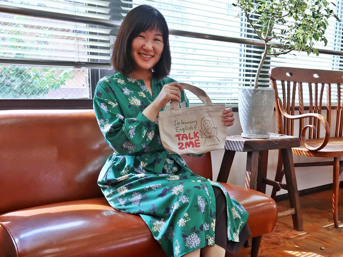 「TALK 2 ME(私に話し掛けて!)」と書かれたオリジナルのバッグを持つ加瀬弘子さん