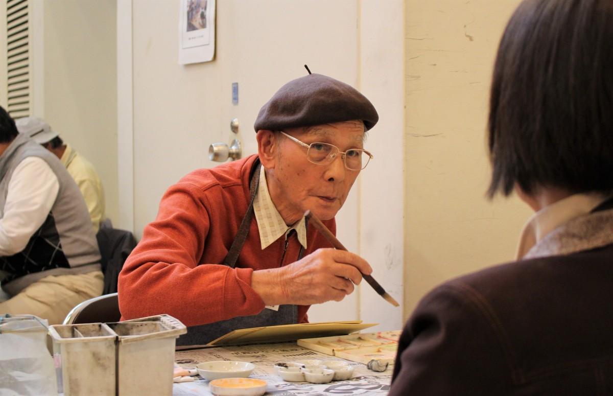 希望者の似顔絵を描く、伊草英男さん