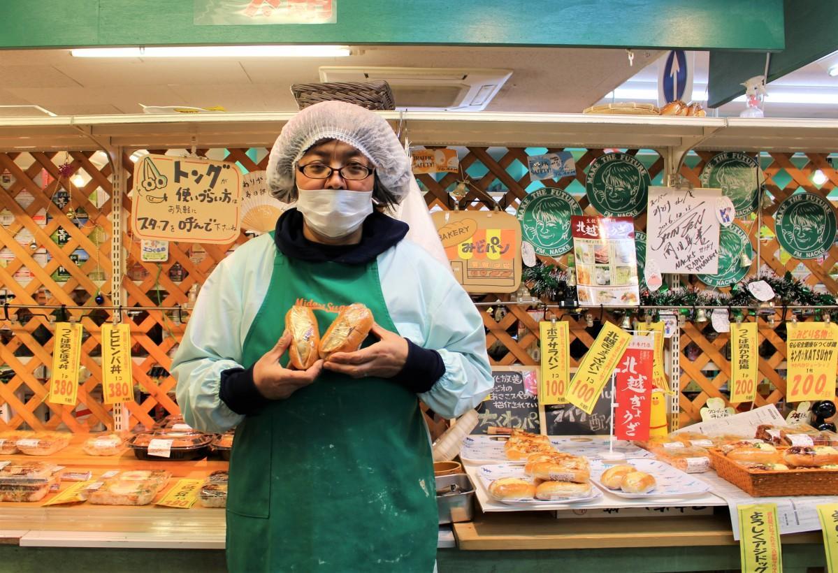 「北越ぎょうざパン」を持つ、みどりスーパー総菜部の河内みどりさん