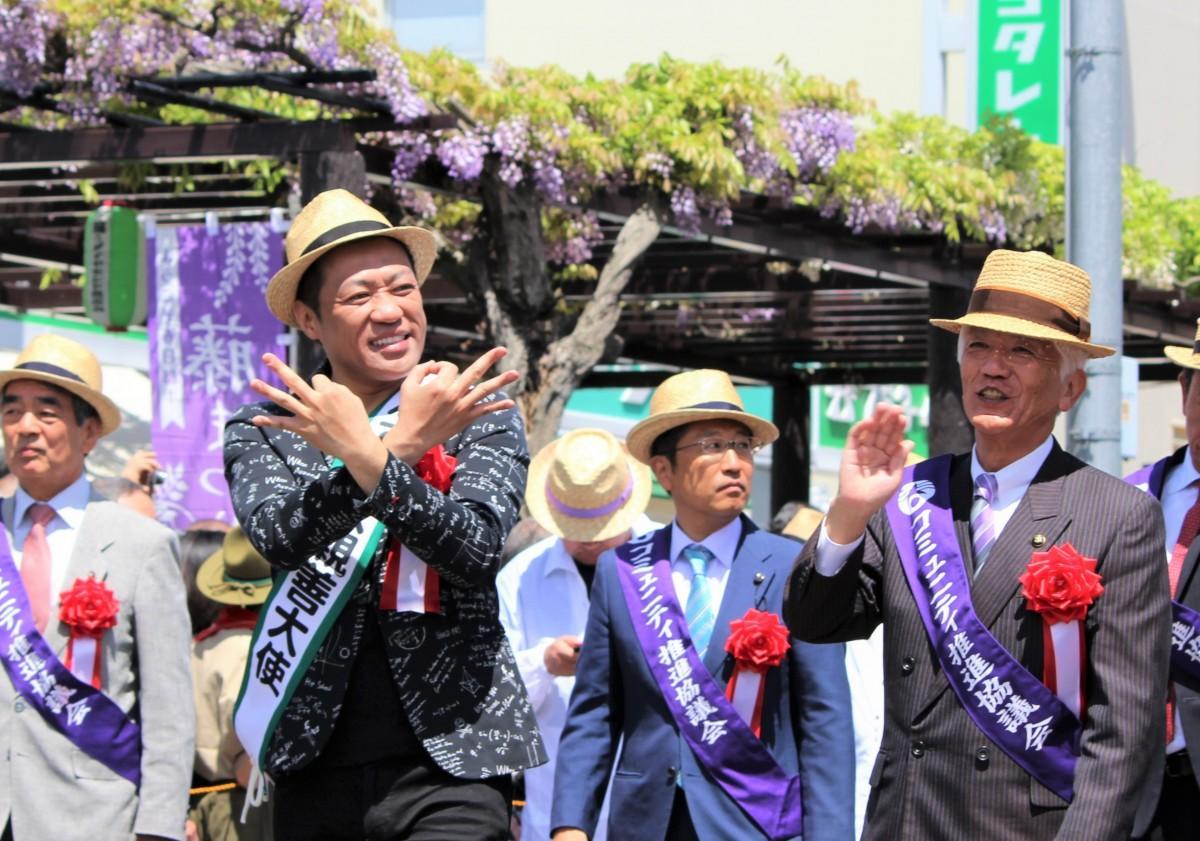 「埼玉ポーズ」でふじ通りを歩くはなわさんと石川市長(右)ら