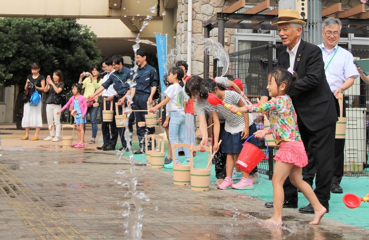 柄杓で水をまく参加者と石川市長