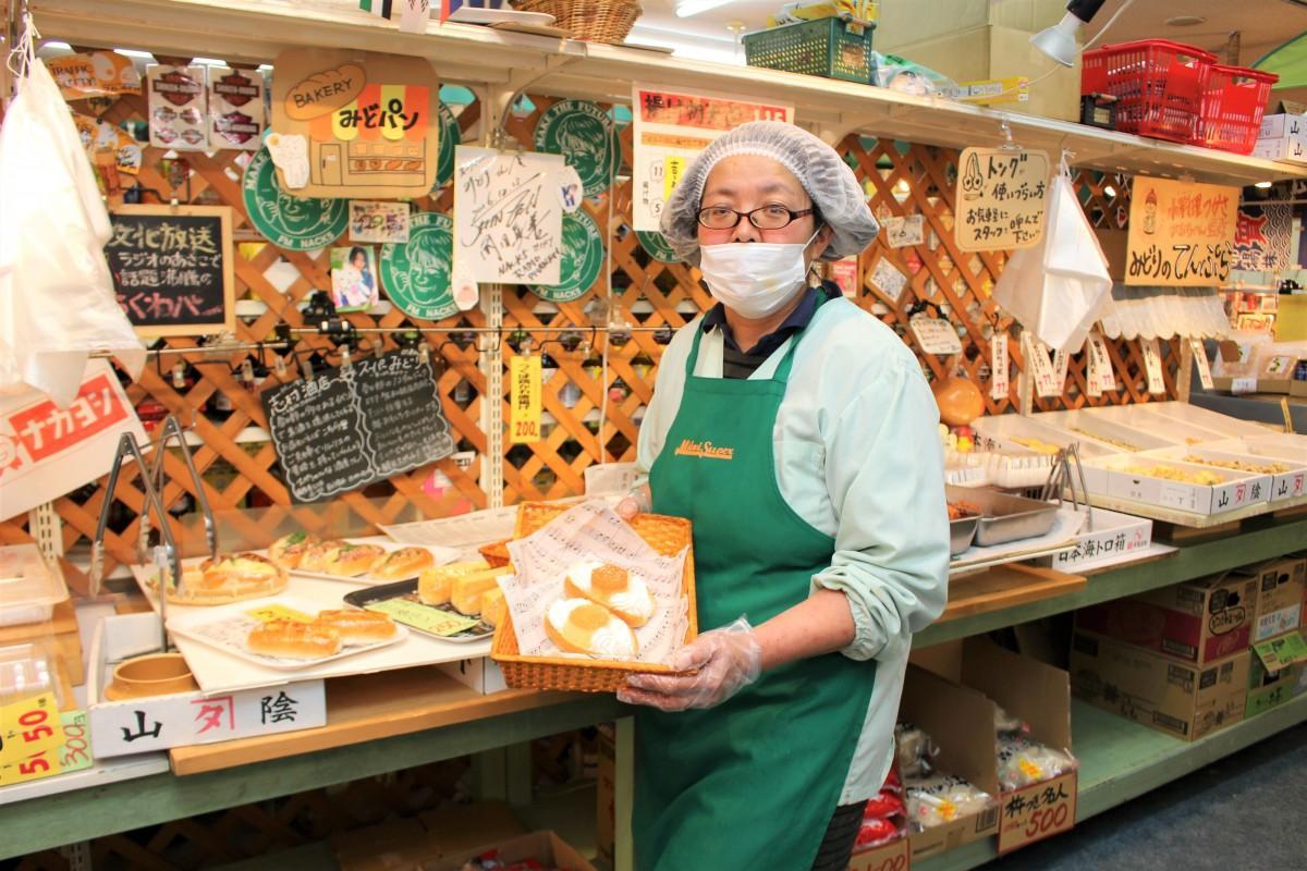 総菜販売エリアで春日部ぷりんパンを持つ河内みどりさん