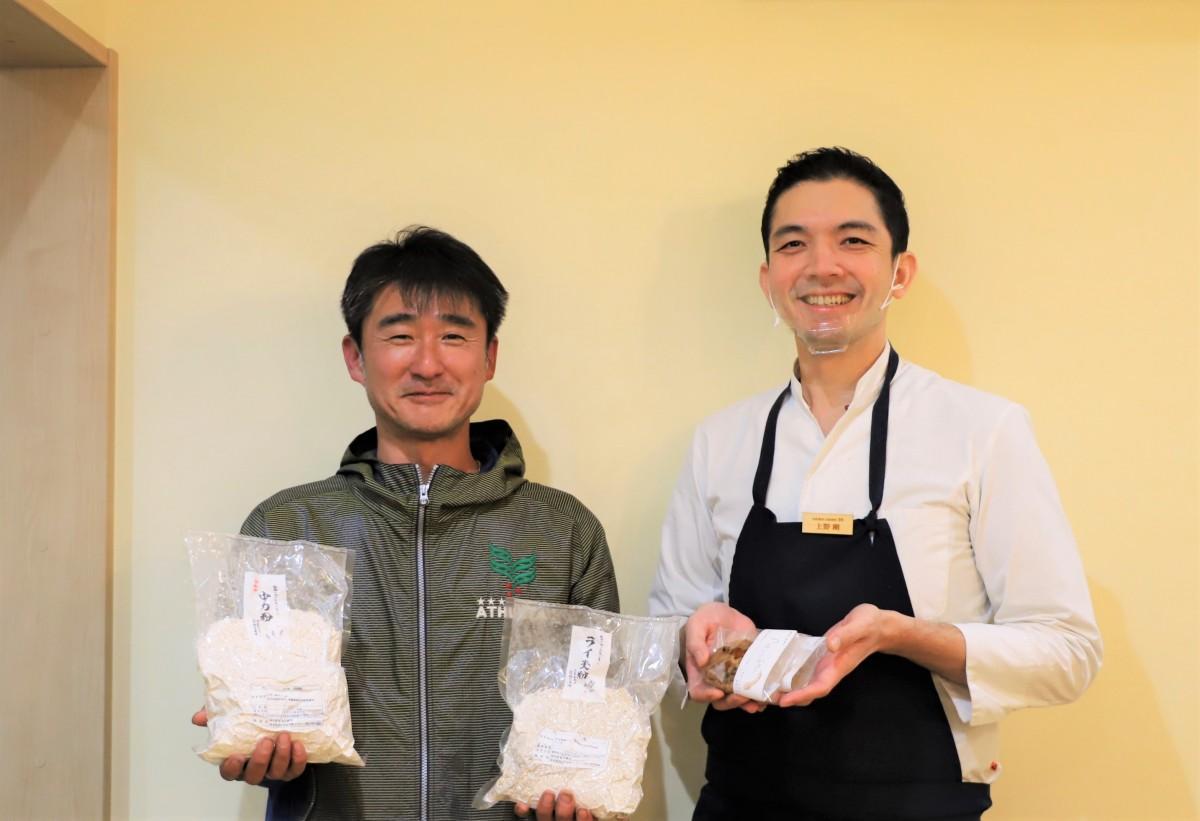 (左から)農場産のライ麦粉と小麦粉を持つ遊佐謙司さん、シェフの上野剛さん