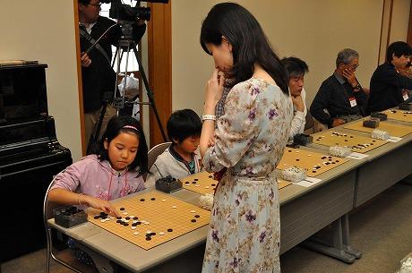 百面打ちを行うプロ棋士と子ども