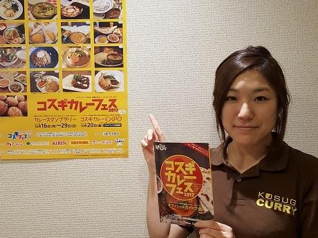 カレーフェスのポスターの前に立つ奥村さん