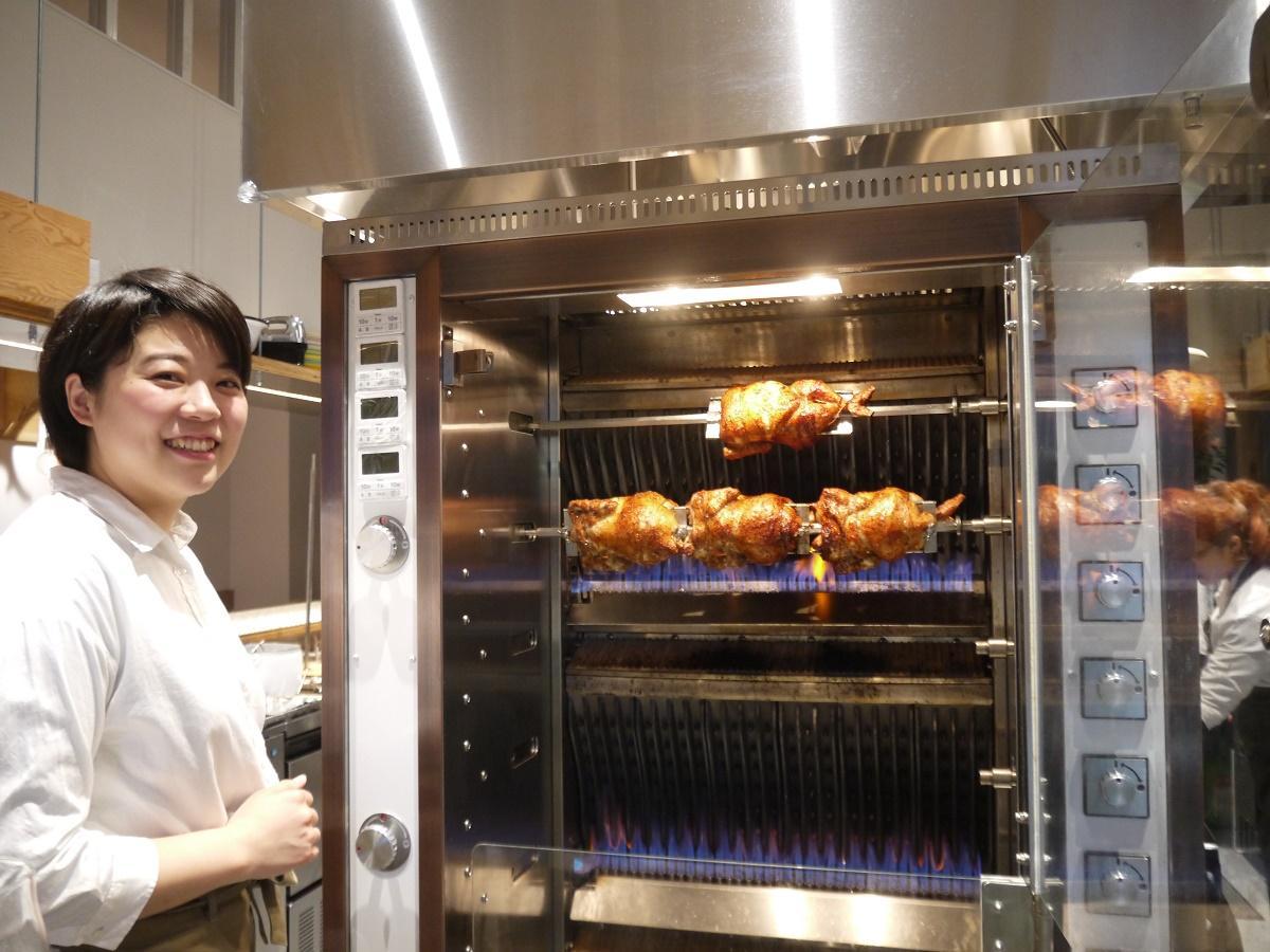 ロティサリーオーブンの前で、スタッフの木村静香さん