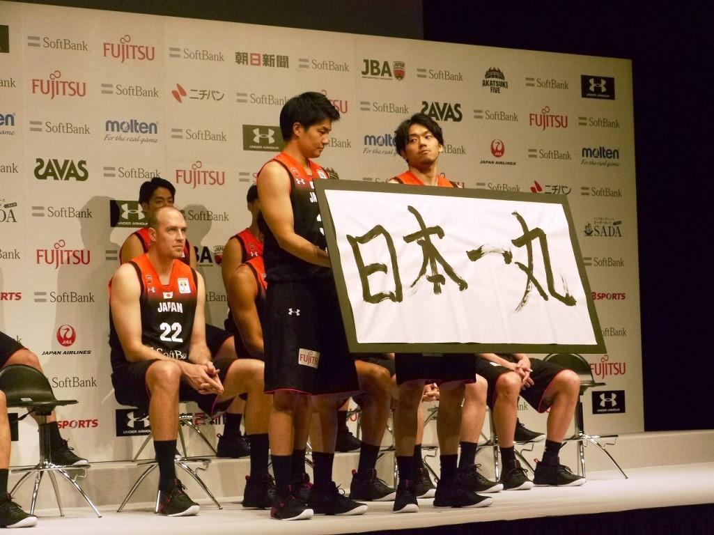 自ら書いた「日本一丸」を披露する篠山竜青選手(前列右)と、その言葉を提案し採用された辻直人選手(前列左)、後ろにニック・ファジーカス選手もおり川崎ブレイブサンダースの3選手
