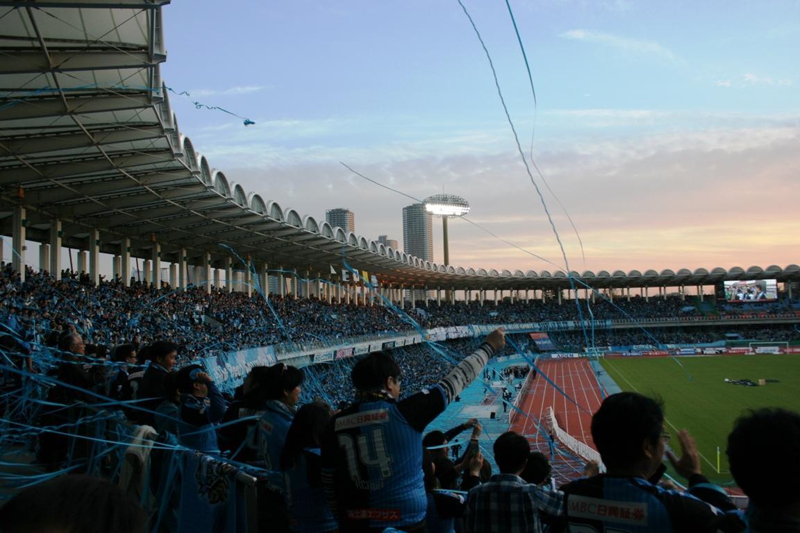 最終節を終えたスタジアムでは改めてフロンターレの優勝を祝う場面が。夕陽に染まるスタジアムに水色のテープが放物線を描く