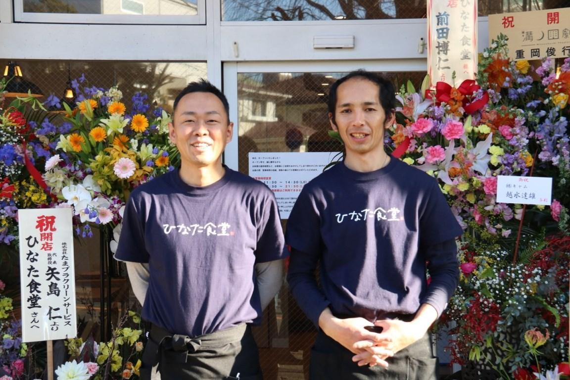 オープン当日たくさんのお祝いの花が届く(左は田中洋平社長、右は内田徹店長)