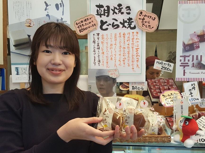 新岩城菓子舗の名物「朝どら」を手にPRをする川崎市文化財団の職員