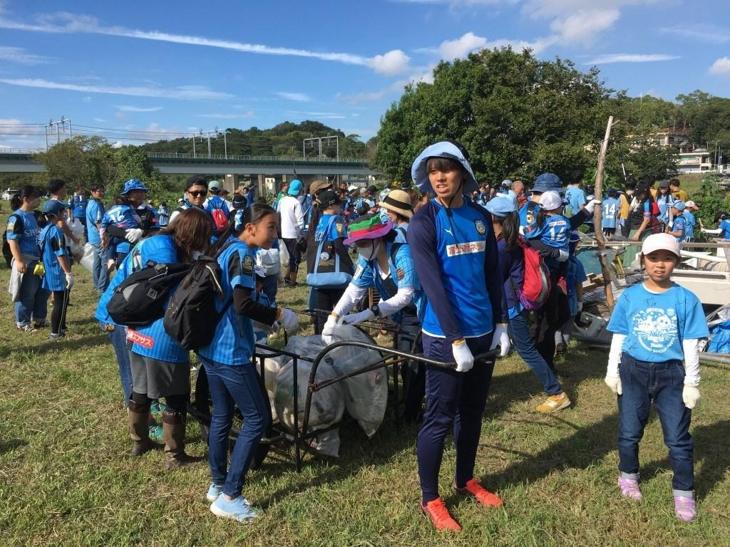子どもたちと一緒に拾ったゴミを運ぶ田中碧選手