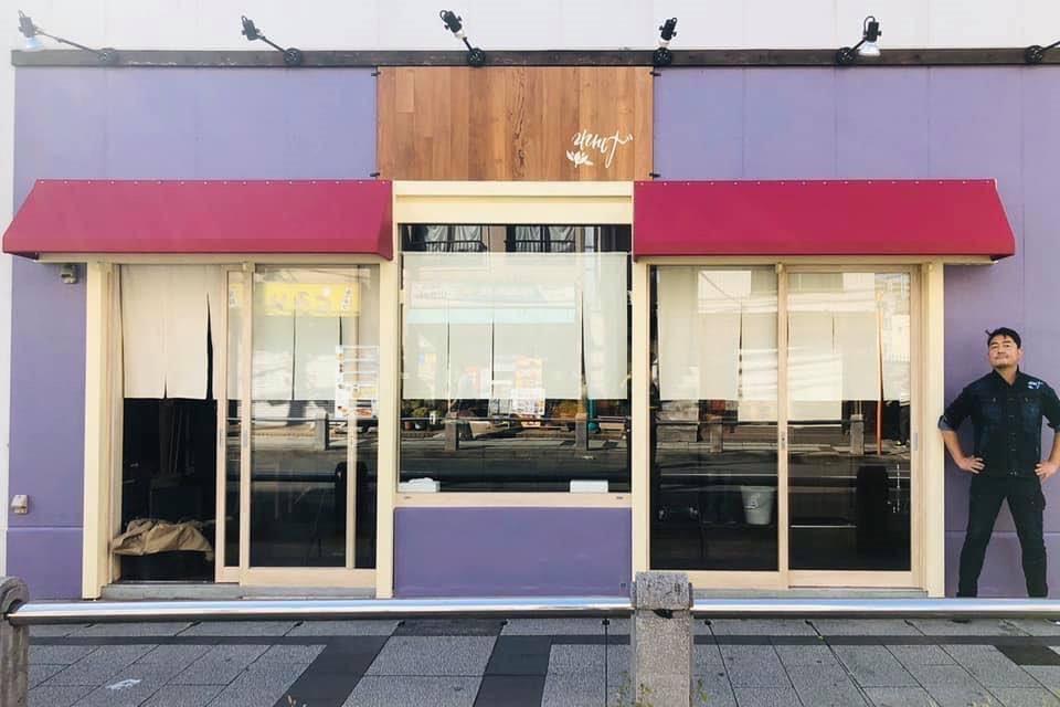 れんげの紅紫色を基調にした店に立つ店主の田中謙次さん