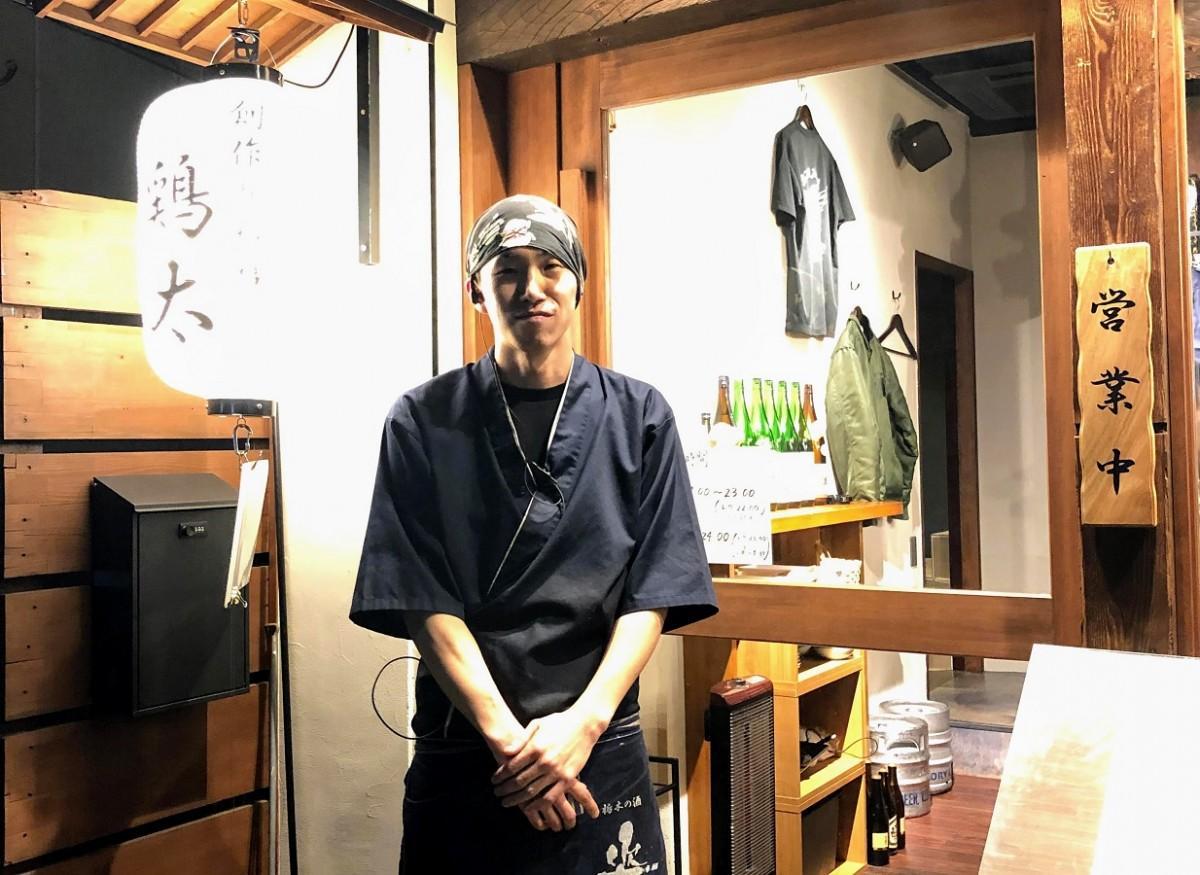 店舗の前で、店主の小松さん