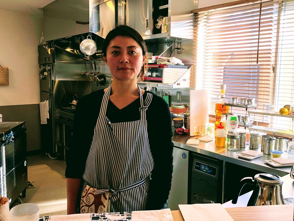 カフェの厨房(ちゅうぼう)に立つ店主の小坂さん