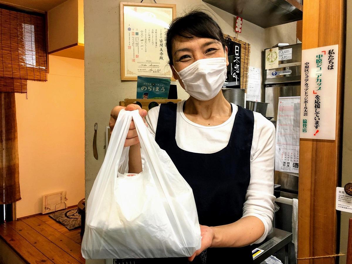テークアウトのお弁当を手渡す店主の笹間美香さん