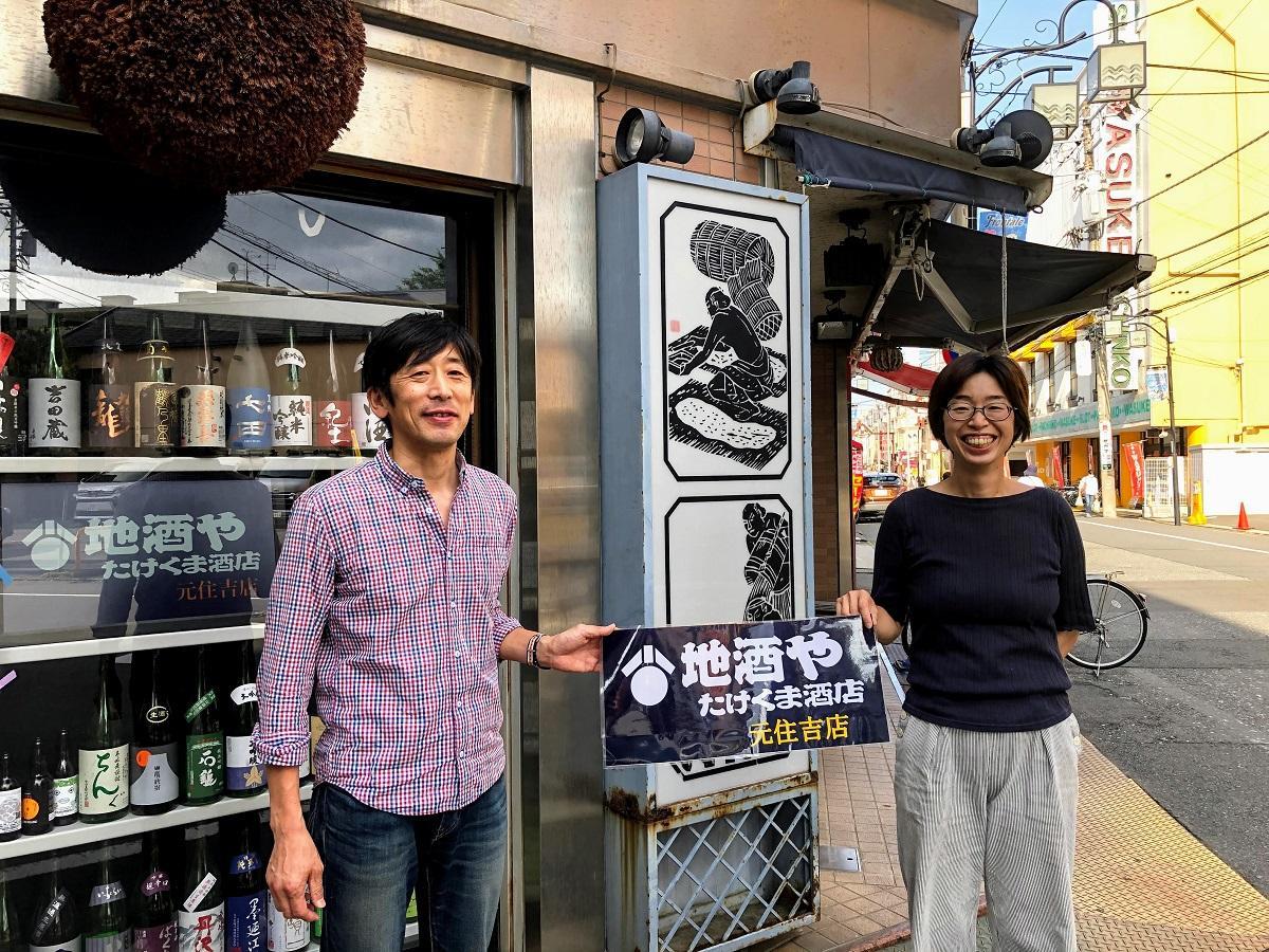 店頭で、たけくま酒店の宮川大祐さんと史恵さん夫妻。「オープンを急いだので、看板もまだ印刷してパウチしただけ」と笑顔を見せる