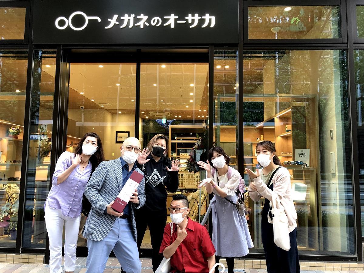 「メガネのオーサカ」に開店祝いに訪れた顧客らと大坂さん(左から二人め)