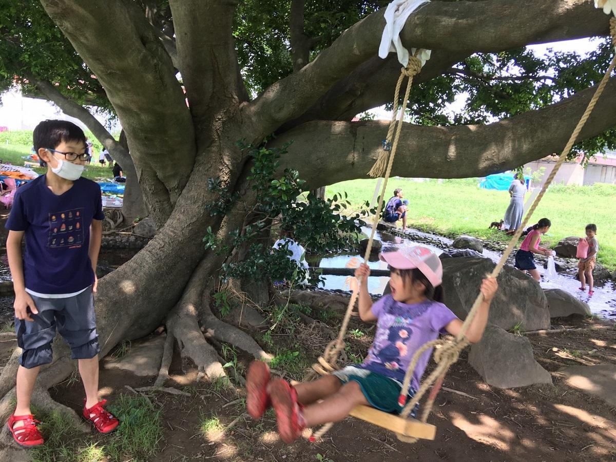 木にブランコをつるして楽しむ子どもたち