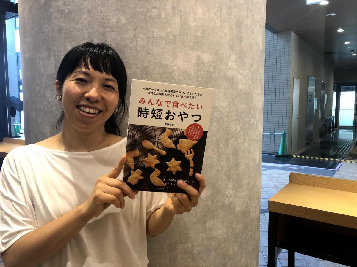 再刊された「みんなで食べたい時短おやつ」を手にする菅野のなさん