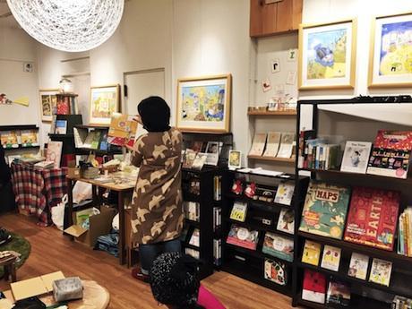 「よもぎBOOKS」で行われている絵本原画展で、絵本作家の出口かずみさんが読み聞かせをする様子