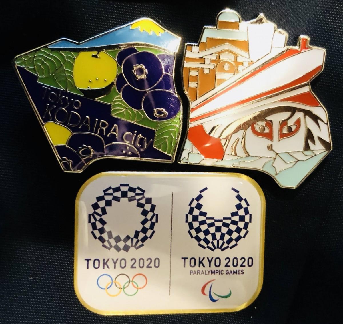 参加賞のピンバッジ。東京2020大会デザインと同市オリジナルデザインの2種類