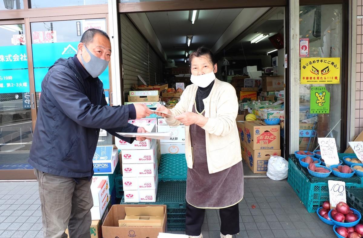 給付金を配る「柳盛会柳沢北口商店街」の橋本直巳会長。5万円を手渡された会員からは「助かります」の声が