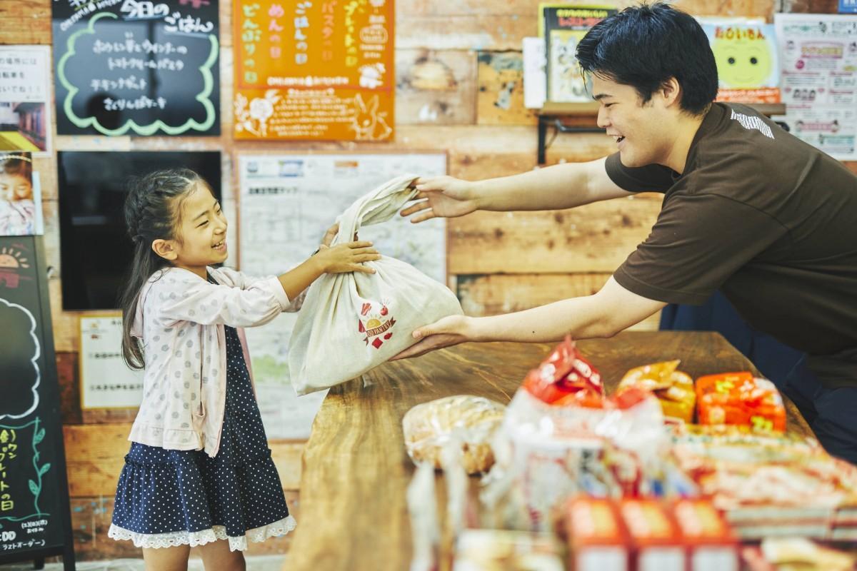 子どもたちに食品を手渡す「おひさまフードパントリー」